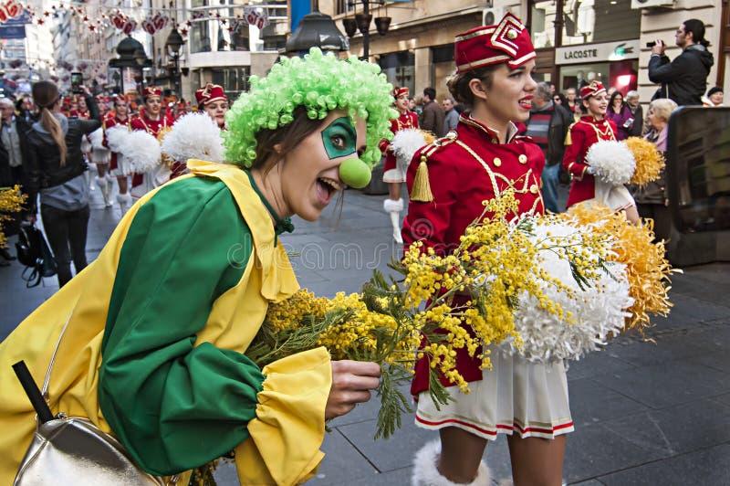Muchacha vestida como payaso con una mimosa y un Majoretts de la flor foto de archivo libre de regalías
