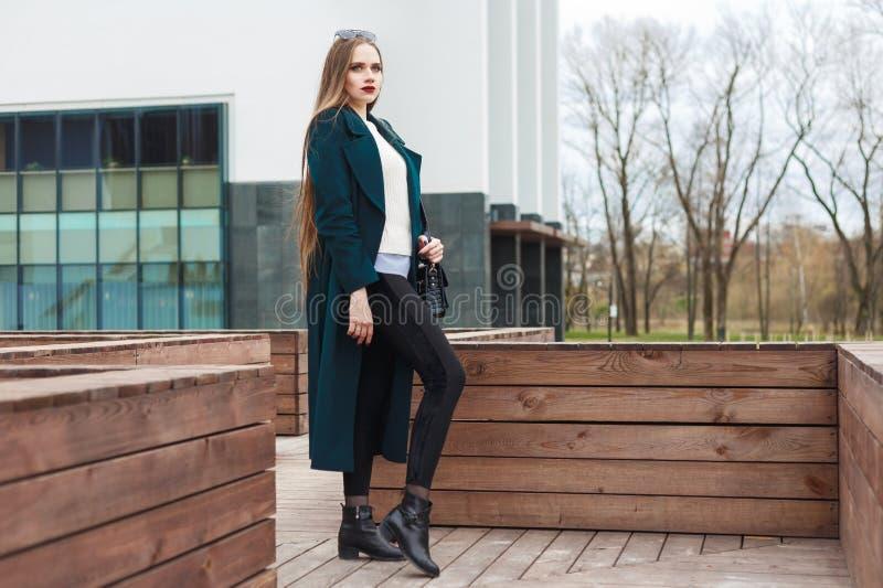 Muchacha vestida de moda en una capa con un bolso en su mano que plantea la colocación en la terraza foto de archivo libre de regalías