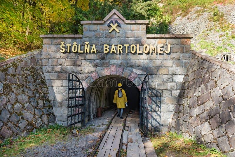 Muchacha vestida en una chimenea minera, con un casco y un paseo de la linterna en el eje de mina Bartolomej imagen de archivo