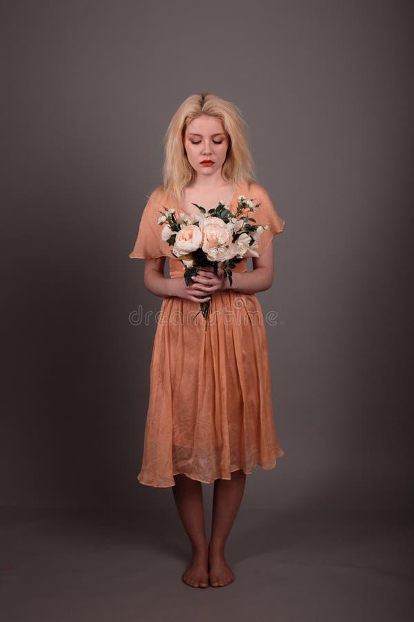 Muchacha viva de la muñeca con las flores en un fondo gris fotografía de archivo libre de regalías