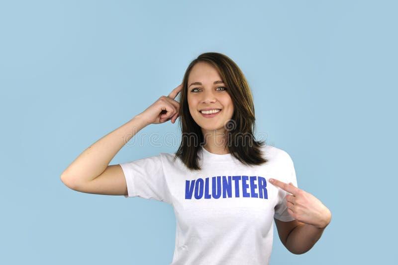 Muchacha voluntaria feliz en fondo azul imagen de archivo libre de regalías