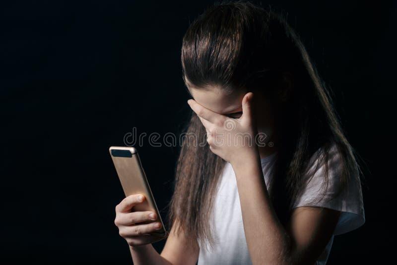 Muchacha vulnerable triste joven que usa el acecho cyberbullying del sufrimiento del abuso en línea asustado y desesperado del te imágenes de archivo libres de regalías