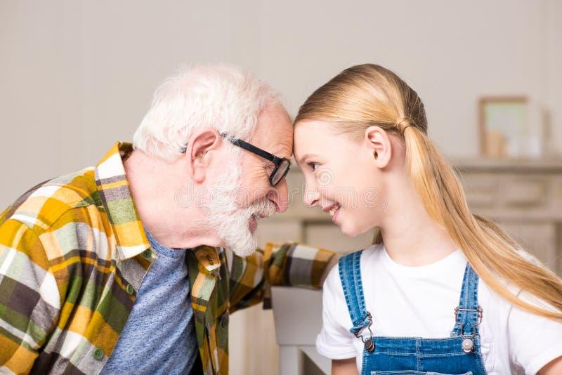 Muchacha y abuelo felices en las lentes que tocan las frentes y que se sonríen imagen de archivo libre de regalías
