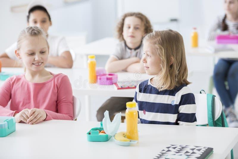 Muchacha y amigo sonrientes que comen el almuerzo en la escuela imágenes de archivo libres de regalías