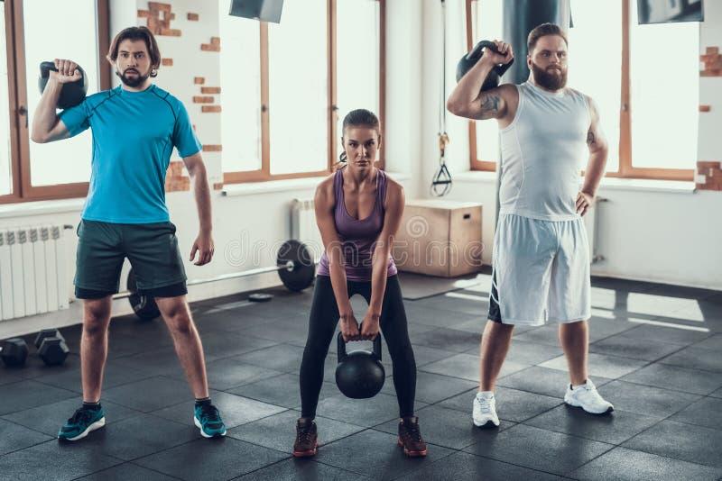 Muchacha y dos individuos que levantan pesos en club de fitness foto de archivo libre de regalías