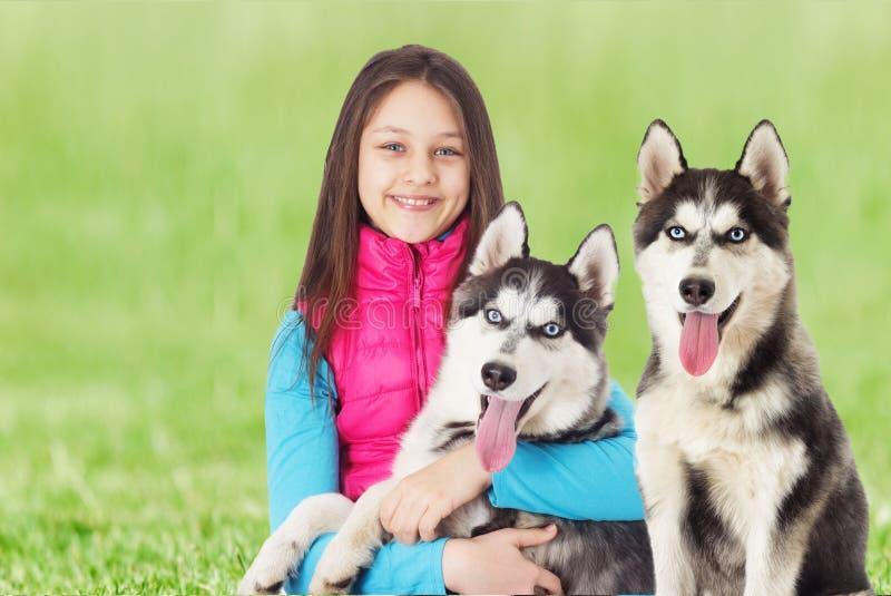 Muchacha y husky siberiano en la hierba verde imágenes de archivo libres de regalías
