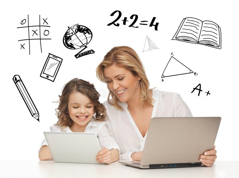 Muchacha y madre con la tableta y el ordenador portátil imagenes de archivo