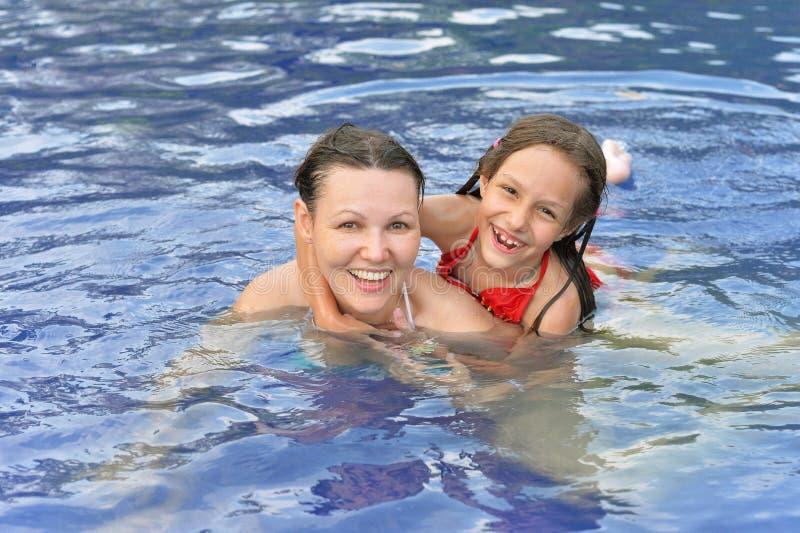 Muchacha y madre felices en piscina fotografía de archivo