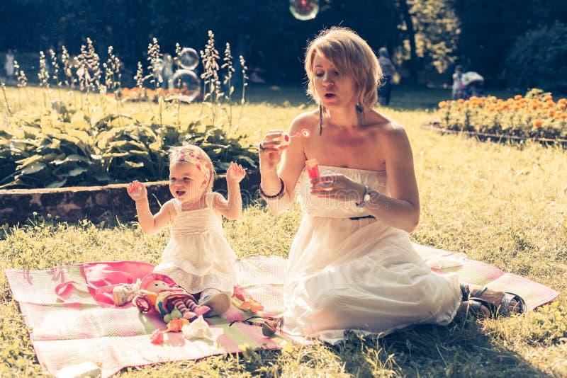 Muchacha y mamá que soplan las burbujas de jabón imagen de archivo libre de regalías