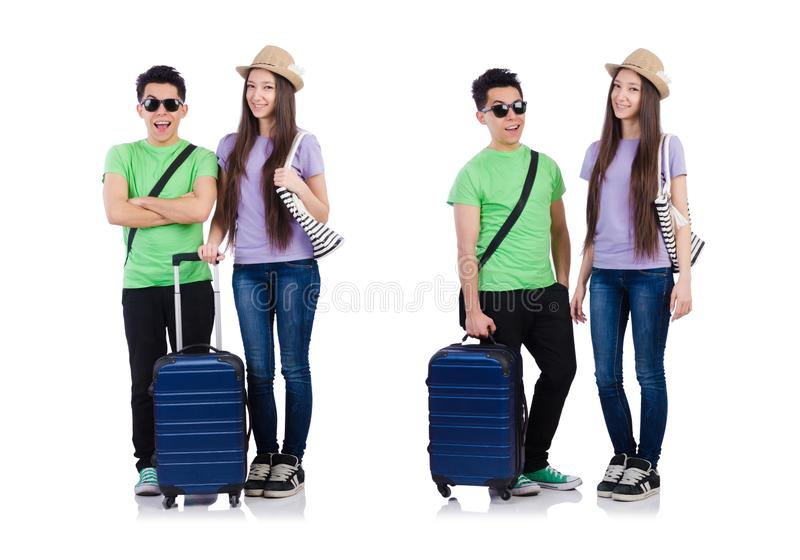 Muchacha y muchacho con la maleta aislada en blanco foto de archivo