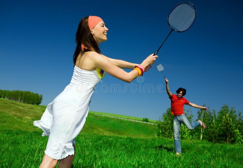 Muchacha y muchacho con las raquetas imagenes de archivo