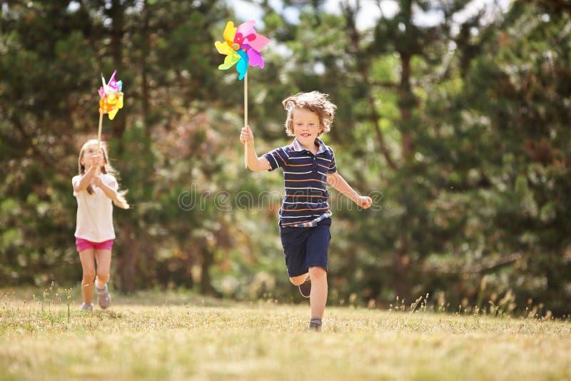 Muchacha y muchacho con los molinillos de viento fotografía de archivo libre de regalías
