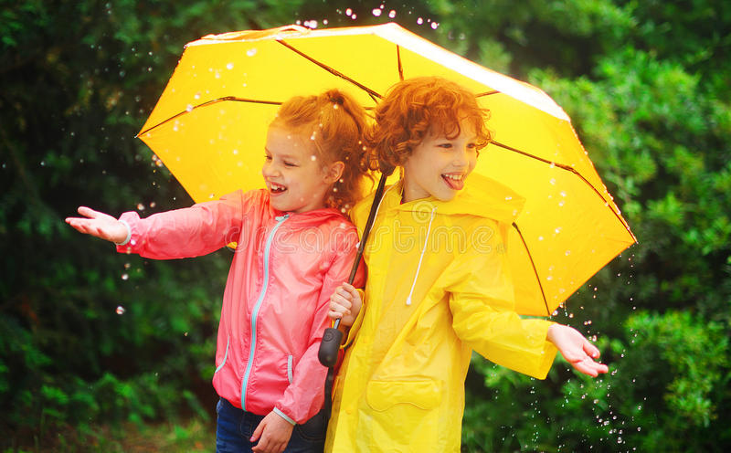 Muchacha y muchacho durante una lluvia debajo de un paraguas imagen de archivo libre de regalías