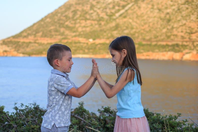 Muchacha y muchacho junto al aire libre pequeño hermano que juega con una más vieja hermana foto de archivo libre de regalías