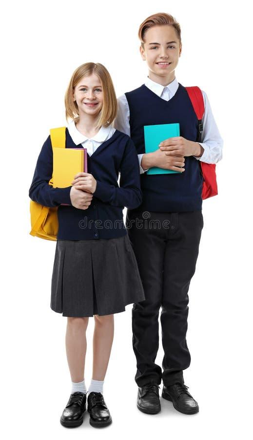 Muchacha y muchacho lindos en el uniforme escolar que sostiene los libros imágenes de archivo libres de regalías