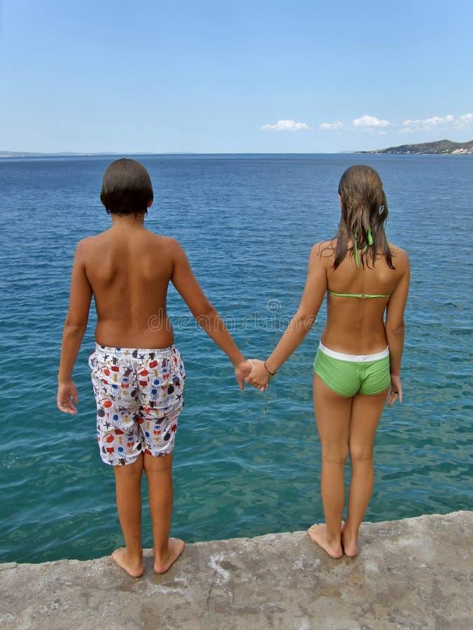 Muchacha y muchacho listos para el salto en el mar adriático fotografía de archivo