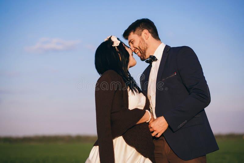 Muchacha y muchacho que abrazan en el campo, la tarde fría, la muchacha en un suéter hecho punto, la gente joven apacible y cariñ imagen de archivo