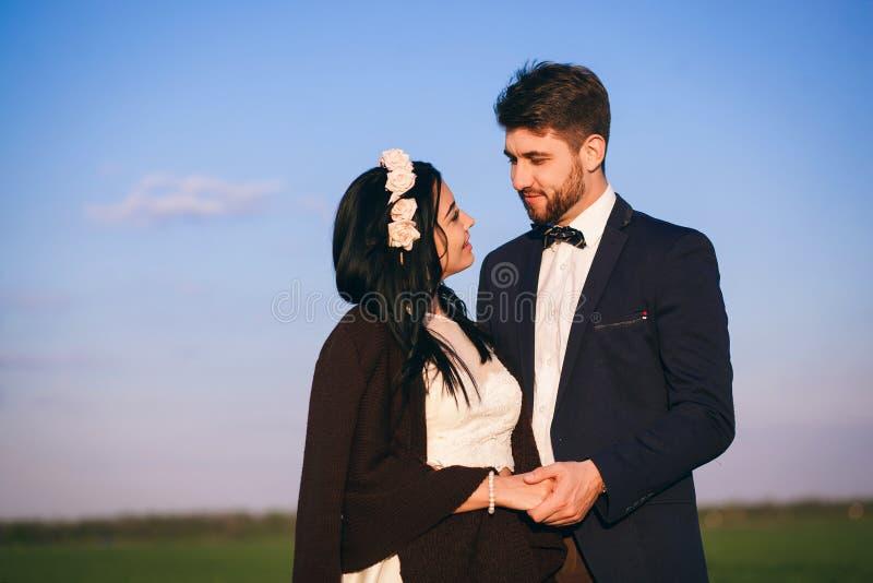 Muchacha y muchacho que abrazan en el campo, la tarde fría, la muchacha en un suéter hecho punto, la gente joven apacible y cariñ imagen de archivo libre de regalías