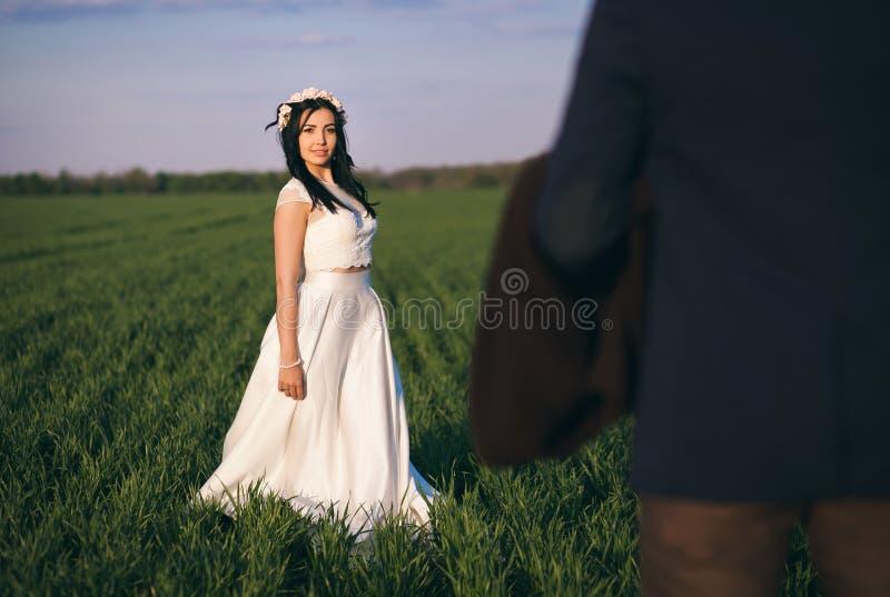 Muchacha y muchacho que abrazan en el campo, la tarde fría, la muchacha en un suéter hecho punto, la gente joven apacible y cariñ imagenes de archivo