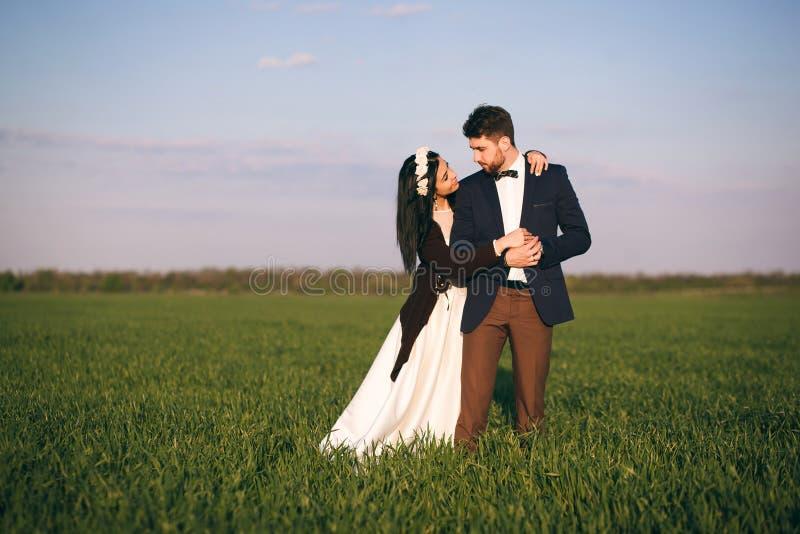 Muchacha y muchacho que abrazan en el campo, la tarde fr?a, la muchacha en un su?ter hecho punto, la gente joven apacible y cari? imágenes de archivo libres de regalías