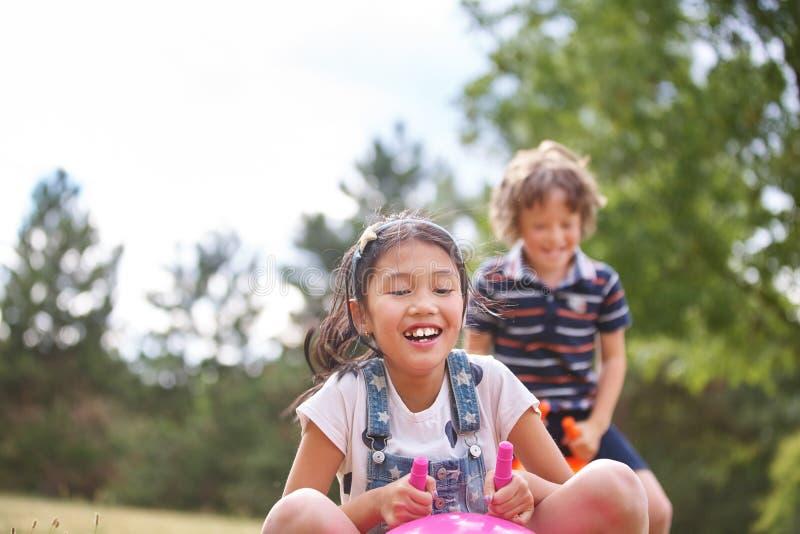 Muchacha y muchacho que juegan con el spacehooper fotografía de archivo