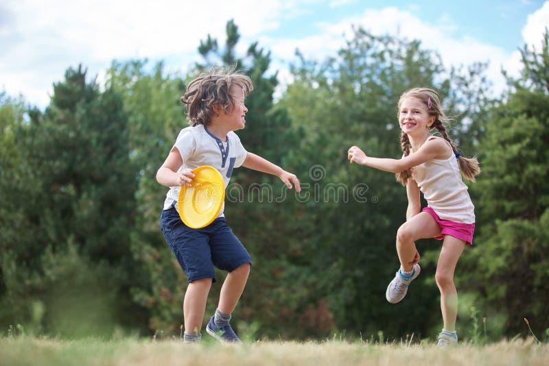 Muchacha y muchacho que juegan el disco volador imagenes de archivo