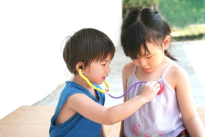Muchacha y muchacho que juegan el estetoscopio imagen de archivo libre de regalías