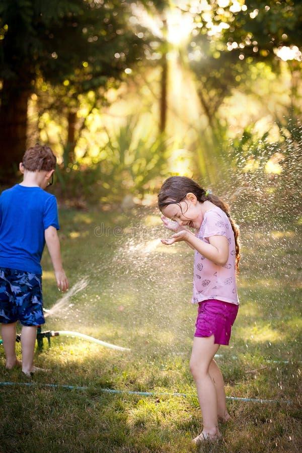 Muchacha y muchacho que juegan en regadera fotografía de archivo libre de regalías