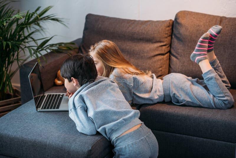 Muchacha y muchacho que usa el ordenador portátil y mintiendo en el sofá imagen de archivo