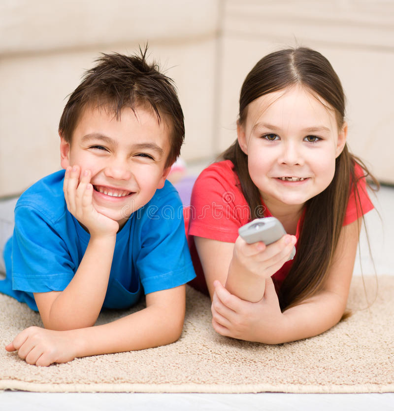 Muchacha y muchacho que ven la TV imagenes de archivo
