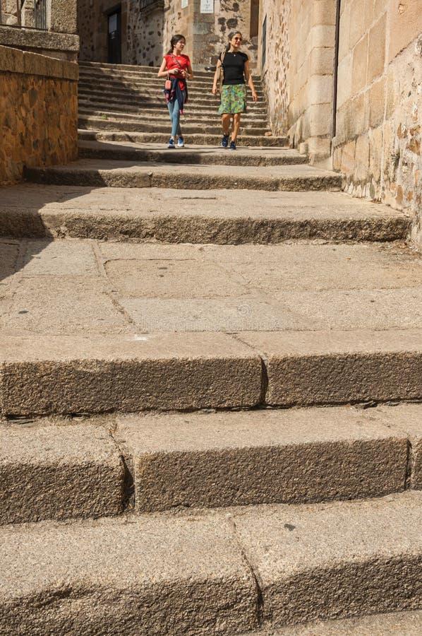 Muchacha y mujer que caminan abajo de las escaleras de piedra en medio de edificios viejos en Caceres imagen de archivo