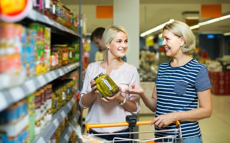 Muchacha y mujer que compran la comida enlatada en el supermercado foto de archivo libre de regalías