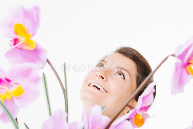 Muchacha y orquídeas sonrientes imagenes de archivo