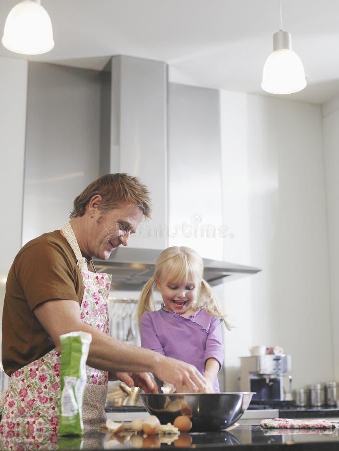 Muchacha y padre Baking In Kitchen imágenes de archivo libres de regalías