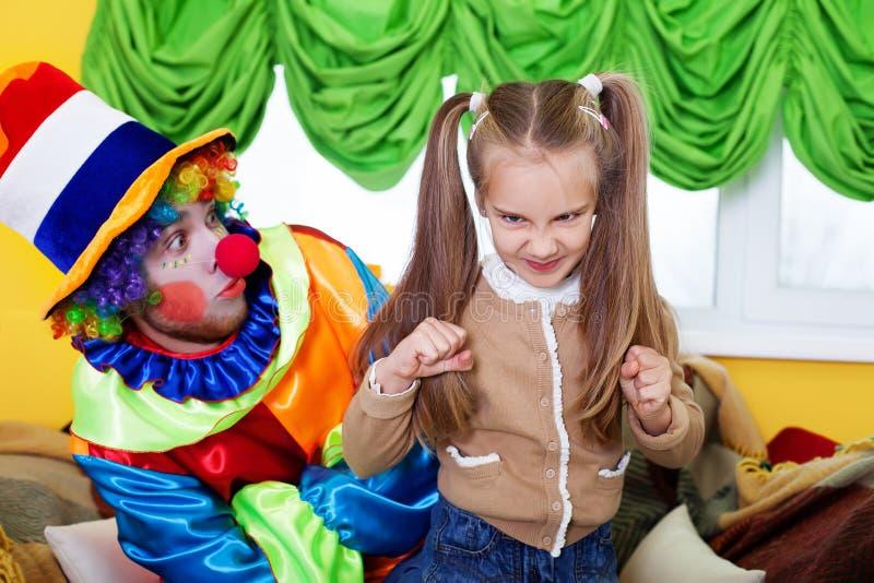 Muchacha y payaso del niño que juegan en fiesta de cumpleaños imagenes de archivo