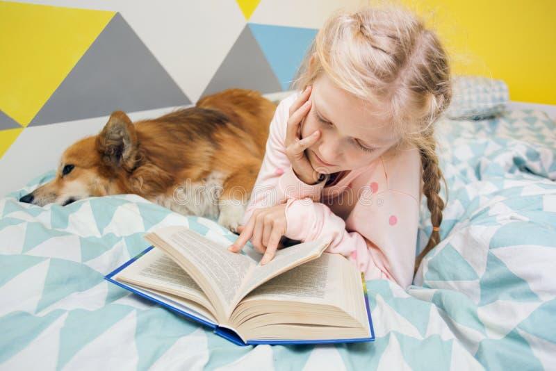 Muchacha y perro en la cama en el cuarto de niños fotos de archivo