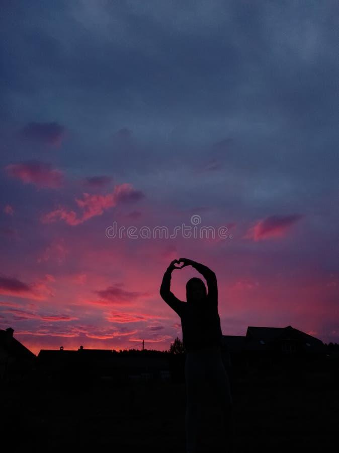 Muchacha y puesta del sol rosada imágenes de archivo libres de regalías