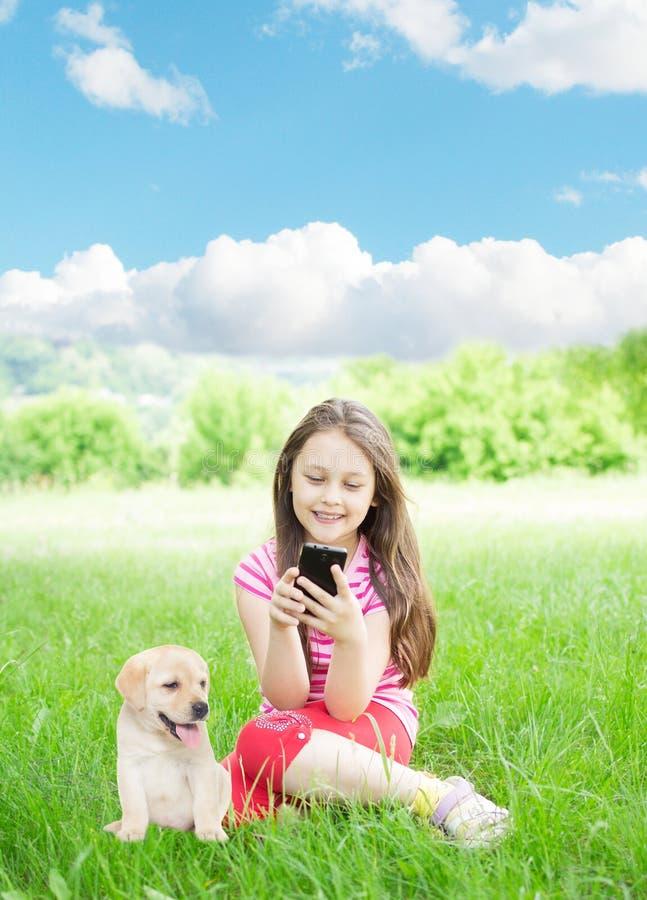Muchacha y smartphone y Labrador imagenes de archivo