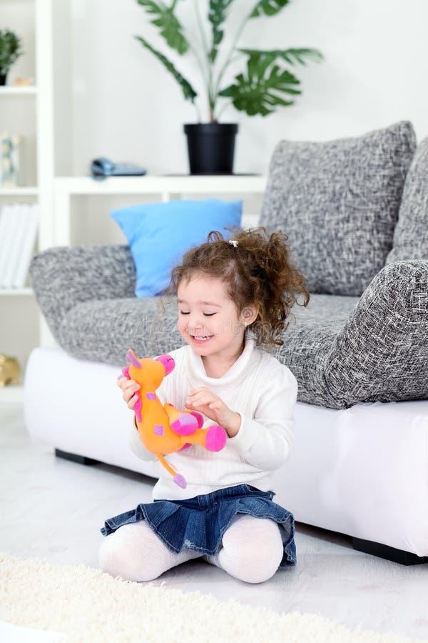Muchacha y su juguete suave preferido foto de archivo