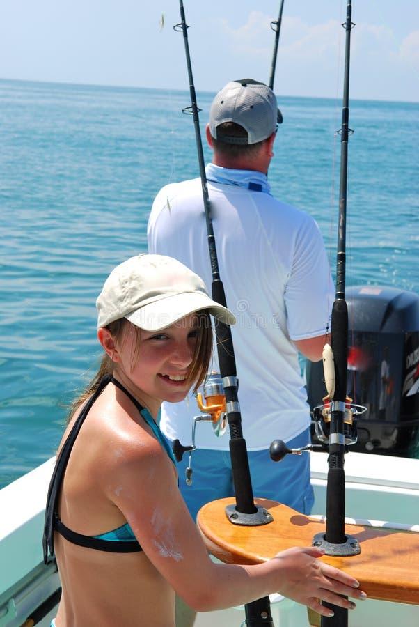 Muchacha y su pesca del padre en un barco fotos de archivo libres de regalías