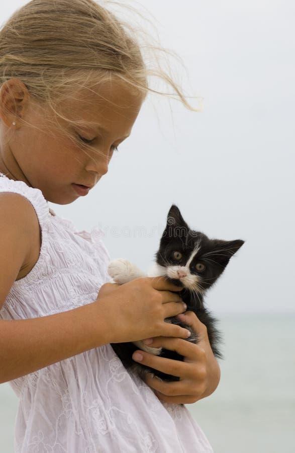 Muchacha y un gatito imagen de archivo