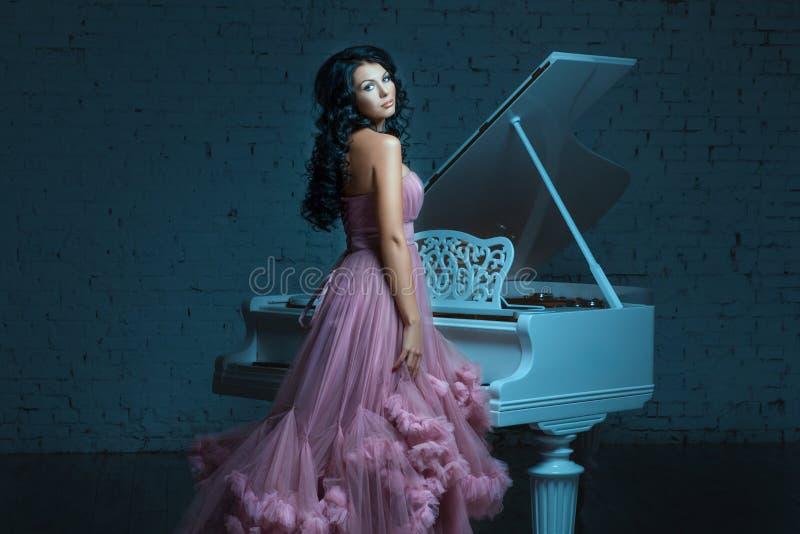 Muchacha y un piano blanco grande imagen de archivo libre de regalías