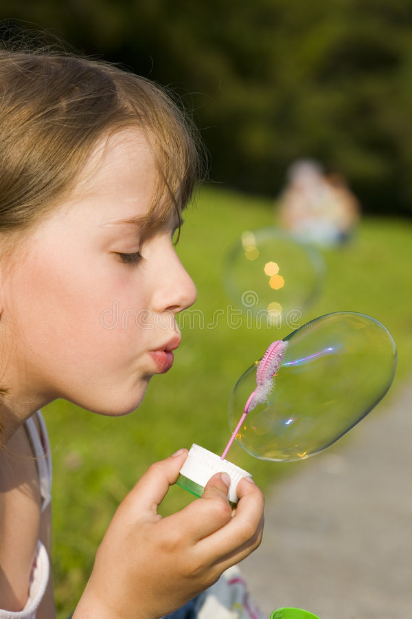 Muchacha y una burbuja de jabón fotografía de archivo