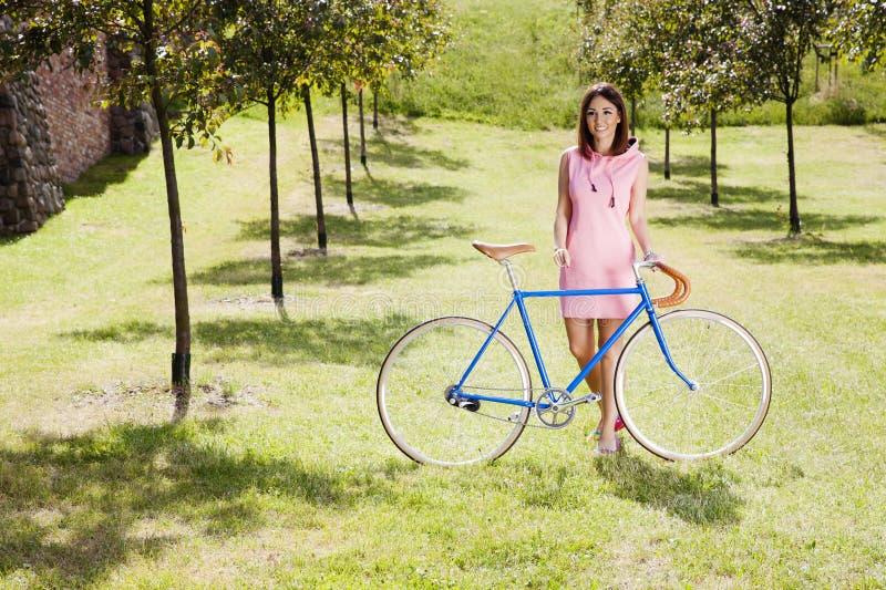 Muchacha y viejo estilo que compiten con la bici imagen de archivo