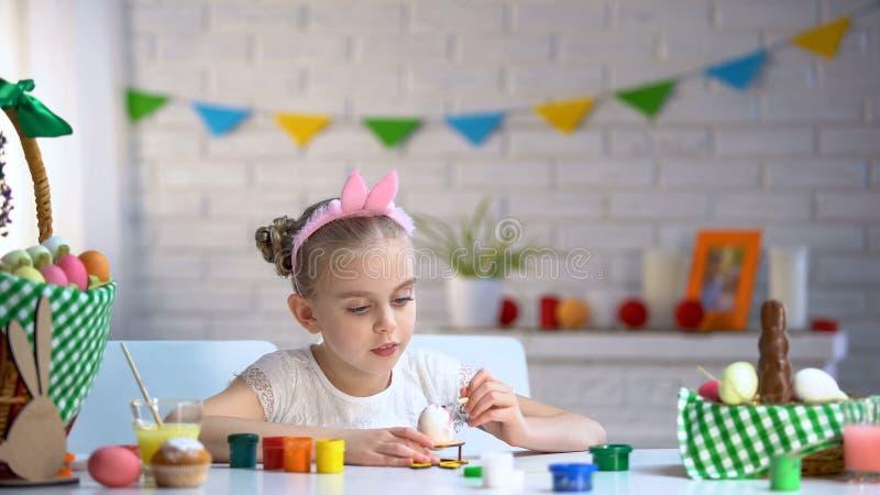 Muchacha zurda que cepilla los huevos de Pascua con la pintura, afición preferida, creatividad imagen de archivo
