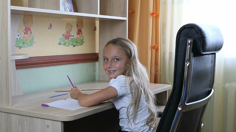 Muchacha zurda que se sienta en silla por la tabla del escritorio y que escribe por la pluma en el cuaderno de papel De nuevo a e fotografía de archivo libre de regalías