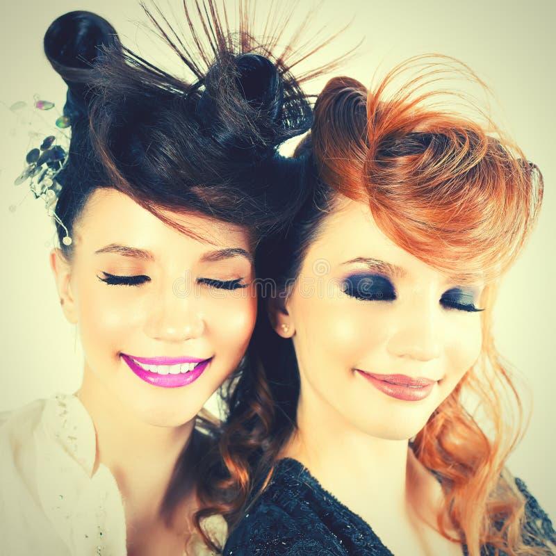 Muchachas absolutamente magníficas de los gemelos con maquillaje y el peinado de la moda imagen de archivo