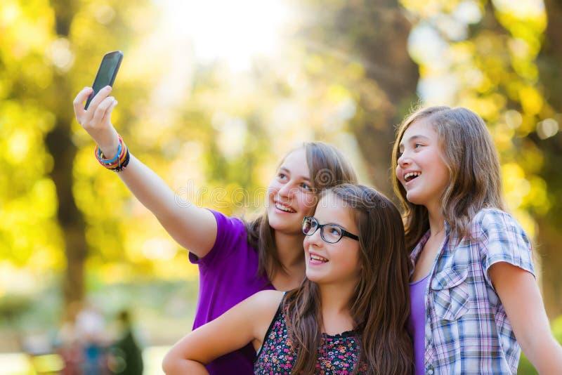Muchachas adolescentes felices que toman el selfie en parque imagen de archivo libre de regalías