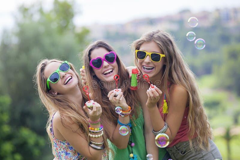 Muchachas adolescentes que soplan burbujas fotografía de archivo