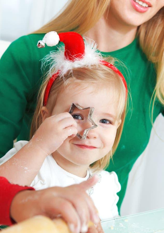 Muchachas adorables con sus galletas de la Navidad de la hornada de la madre en la k foto de archivo